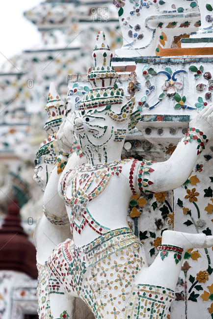 Close-up view of patterned wall of Wat Arun temple in Bangkok with paintings and statues