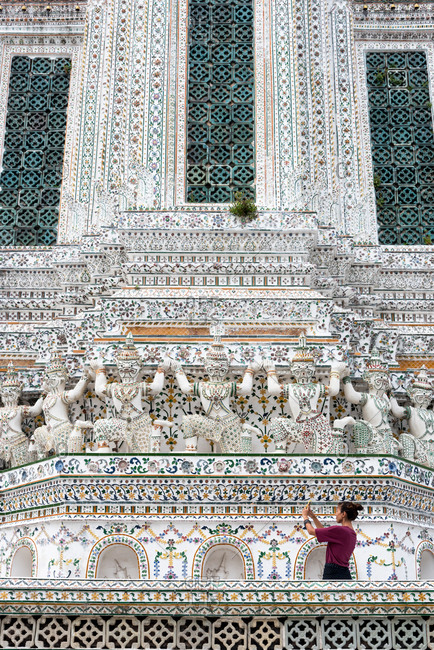 Back view of tourist taking photo of beautiful ornamental wall of Wat Arun temple in Bangkok