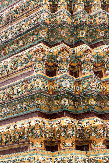 Close-up view of ornamental wall of Wat Arun temple in Bangkok with flower pattern