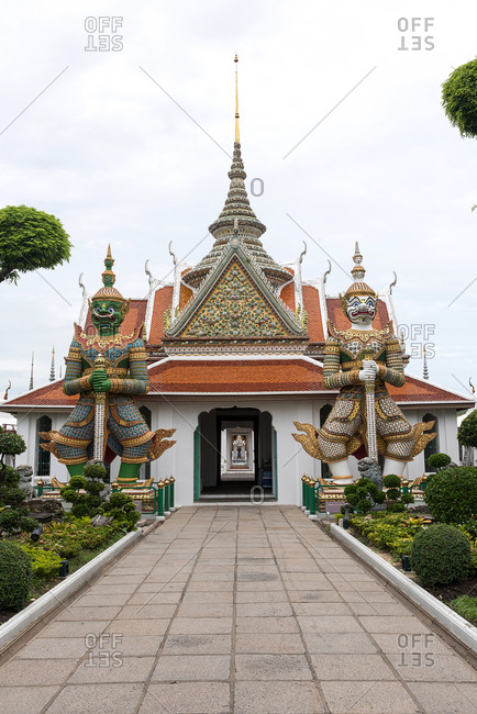 Beautiful Wat Arun Buddhist temple with two demon guardians placed near entrance in garden with green trees and bushes