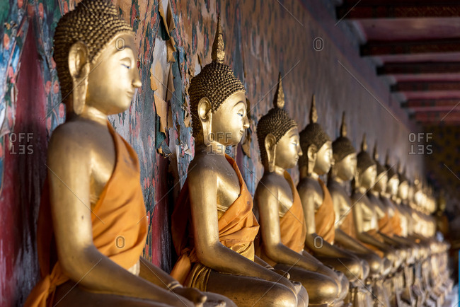 Golden similar statues of Buddha placed in line near patterned wall in Buddhist temple