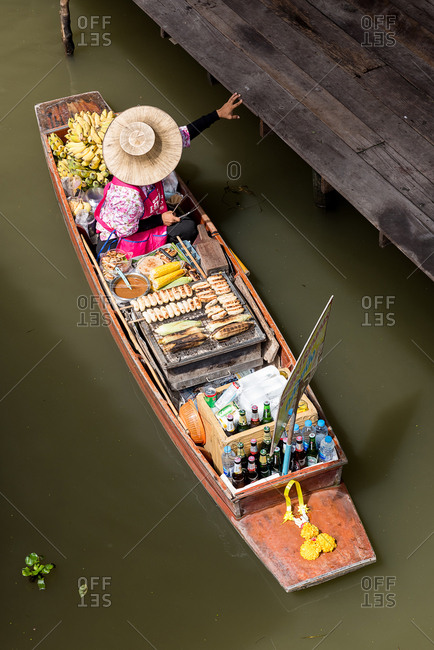From above view of Thai seller sitting in boat full of food for sale in floating market