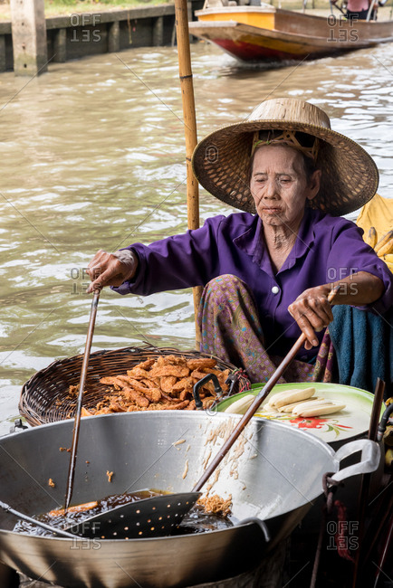 Thai old woman in purple blouse and hat sitting in boat floating on dirty river and cooking national food in big metal dish