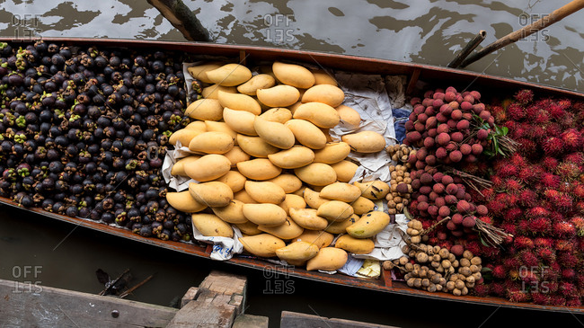 From above view of tropical fruits placed in boat for selling in floating market