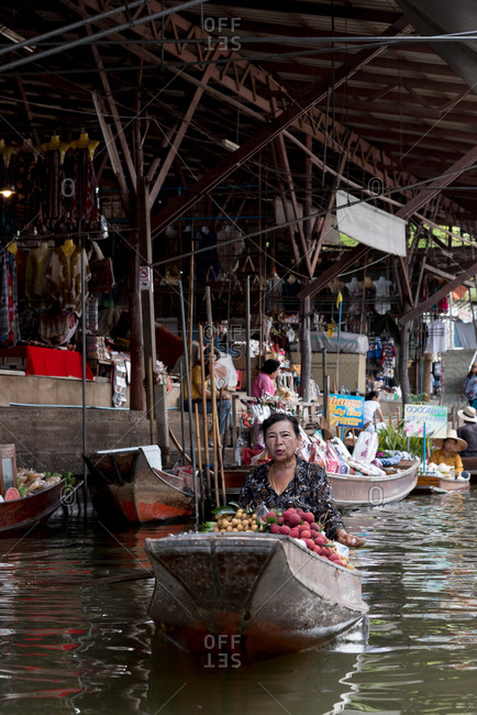 Seller sailing in boat full of young coconuts for sale in floating market