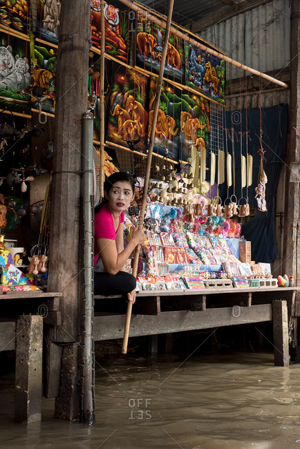 Side view of Thai woman sitting on wooden shelf of souvenir store with national goods in floating market