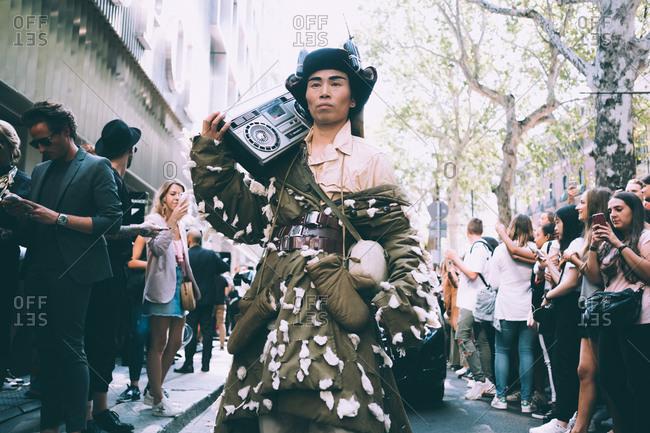 MILAN, ITALY - SEPTEMBER 23, 2018: Peculiar asian fashion model with stereo attending fashion show during Milan Fashion Week Women Spring/Summer 2019