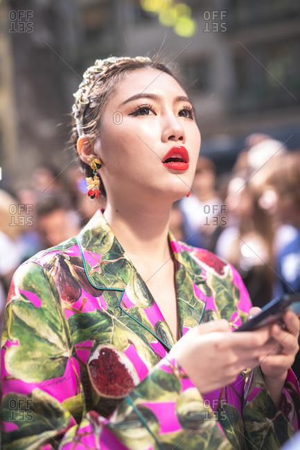 MILAN, ITALY - SEPTEMBER 23,  fashionable woman using smart phone attending fashion show during Milan Fashion Week Woman Spring/Summer 2019