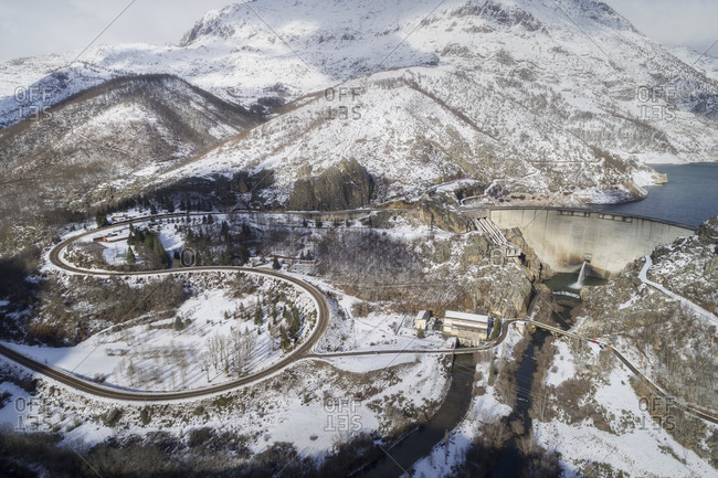Aerial view of reservoir with dam and snow covered mountains in winter, Crimenes, Castile and Leon, Spain