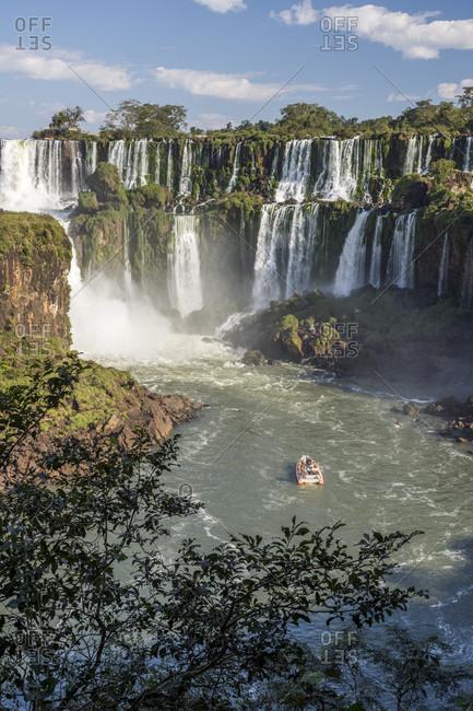Boat in front of splashing Iguazu Falls during tour, Parana, Brazil