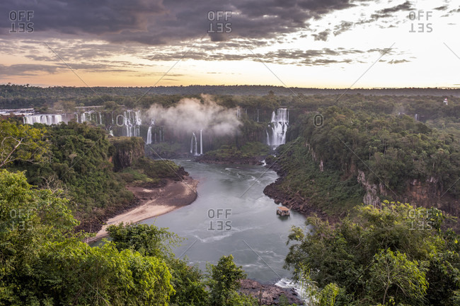 Scenic view of rainforest surrounding splashing Iguazu Falls at dusk, Parana, Brazil