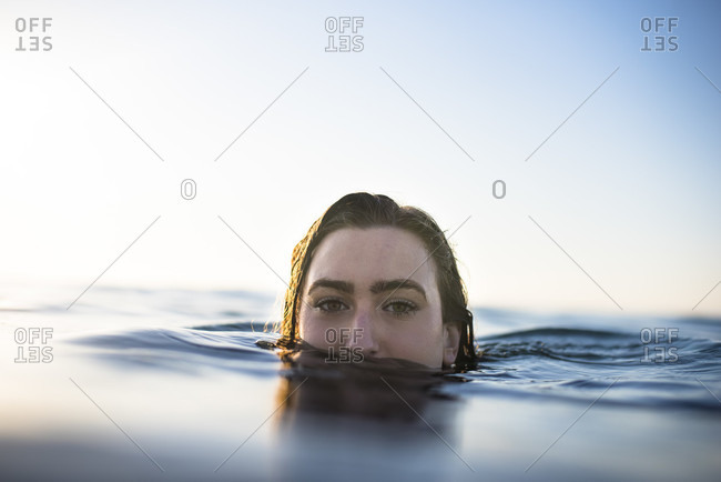 High section shot of young woman swimming in sea face deep in water