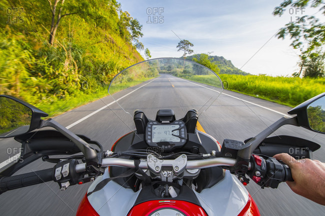 Personal perspective of biker riding on empty countryside highway,?Chiang Rai,?Mueang Chiang Rai District, Thailand