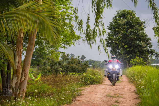 Man riding motorcycle on empty dirt road toward camera,?Chiang Mai,?Mueang Chiang Mai District, Thailand