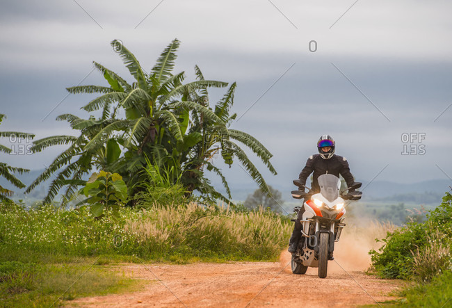 Biker raising dust on empty countryside dirt road,?Chiang Mai,?Mueang Chiang Mai District, Thailand