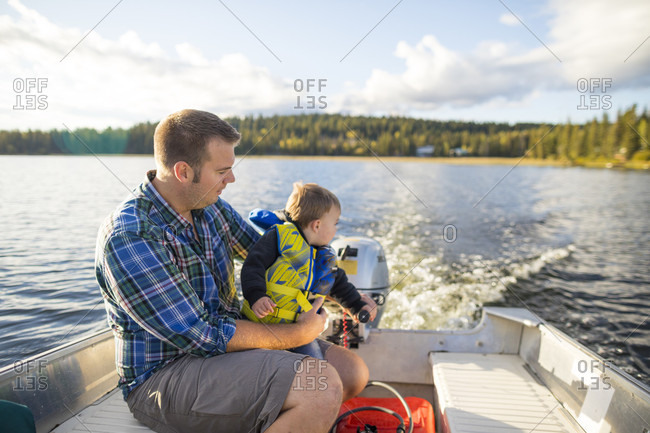 View of father and son spending time together on motorboat in lake, Kamloops, British Columbia, Canada