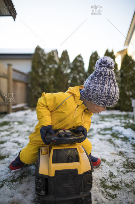 Front view of toddler riding toy car in backyard in winter