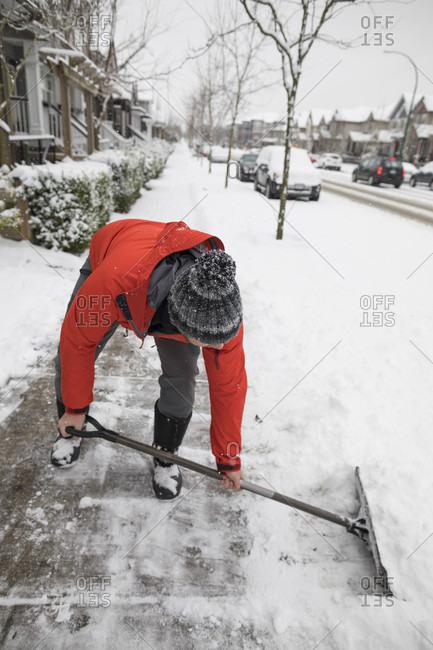 Full length shot of man shoveling snow off sidewalk in winter in suburb