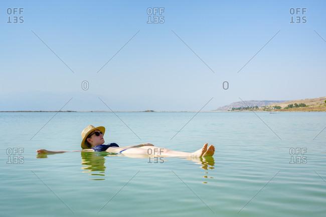 Side view of woman floating on back in Dead Sea, Ein Bokek, Southern District, Israel