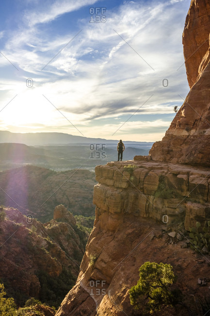 Distant view of female hiker standing at Cathedral Rock in Sedona, Arizona, USA