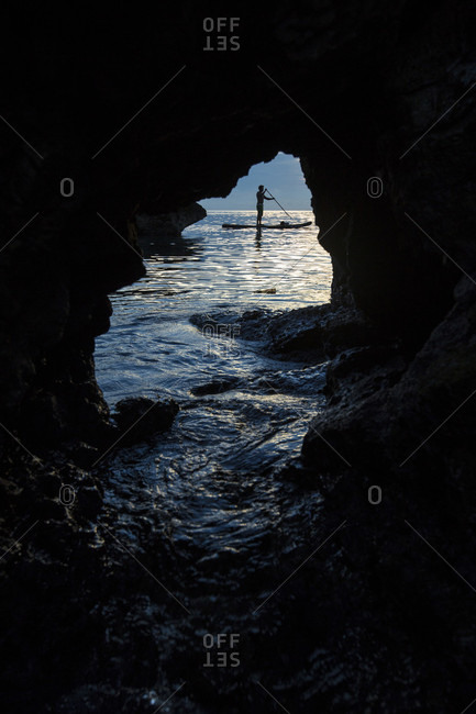 View from cave of silhouette of man paddle boarding in sea, Misool, Raja Ampat, Indonesia