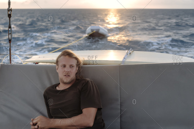 Waist up shot of young man sitting on sailboat