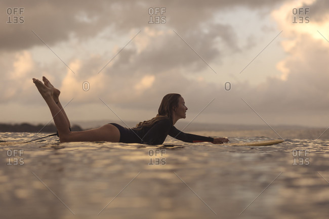 Female surfer lying on surfboard while surfing in ocean at dawn, Kuta, Bali, Indonesia