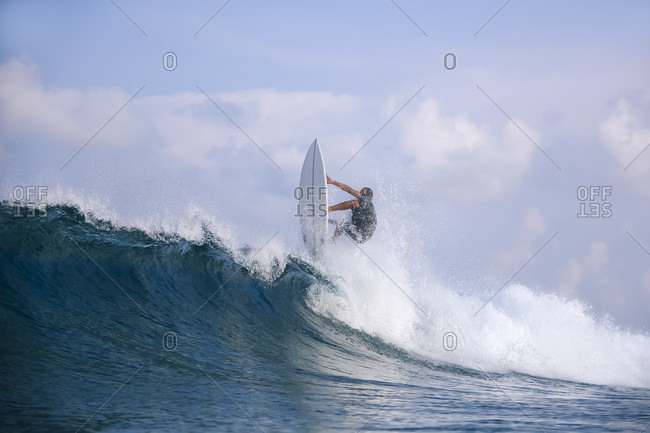 Male surfer riding wave against clouds, Male, Maldives