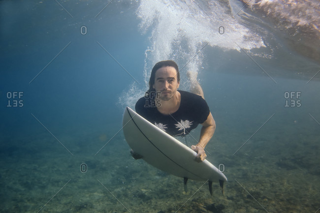 Male surfer looking at camera while diving in ocean, Male, Maldives