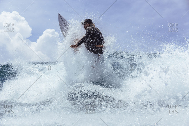Male surfer splashing while riding wave against sky, Male, Maldives