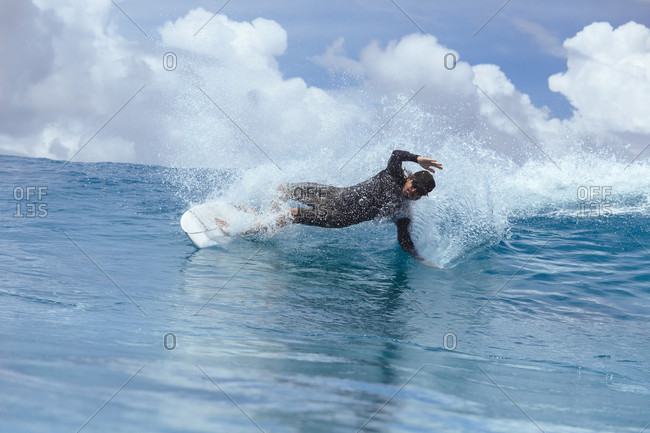Male surfer slanting while riding wave against clouds, Male, Maldives