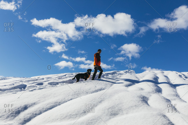 Clouds over man snowshoeing with pet dog on snowcapped hill, Whistler, British Columbia, Canada