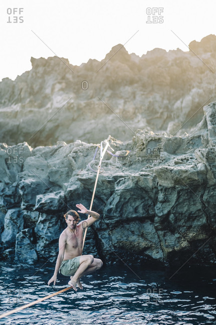 Young shirtless man balancing across tightrope over coastal water, Tenerife, Canary Islands, Spain