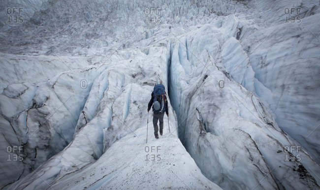Rear view shot of male backpacker hiking across glacier during Mount Robson ascent, British Columbia, Canada
