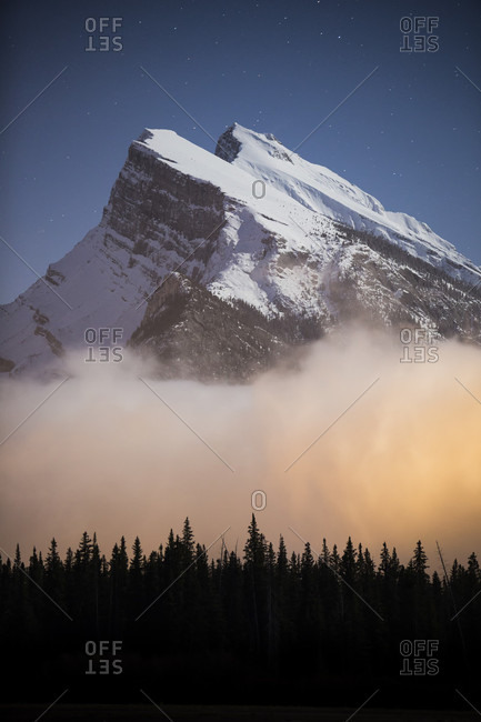 View of snowcapped Mount Rundle at night and silhouette of forest, Banff National Park, Alberta, Canada
