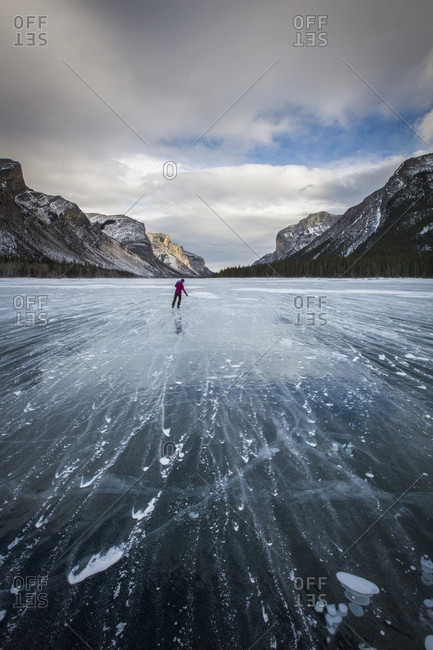 Distant rear view shot of person ice skating on frozen Lake Minnewanka in winter, Banff National Park, Alberta, Canada