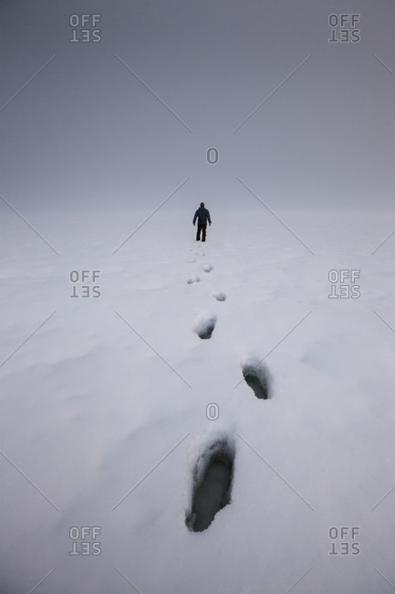 Footprints in snow behind person in winter