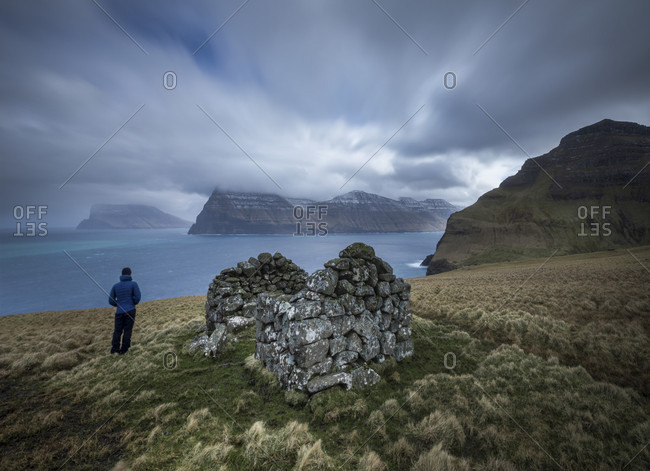 Rear view of person standing on seashore near ruin of building, Kalsoy, Faroe Islands
