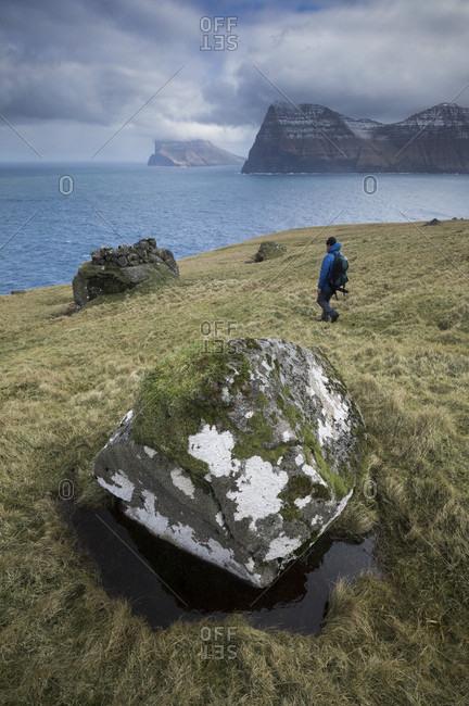 Distant view of backpacker walking on seashore, Kalsoy, Faroe Islands