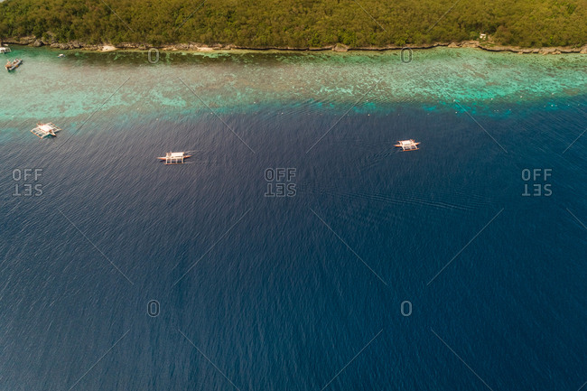 Aerial view of traditional filipino fishing boats by Sumilon island, Philippines.
