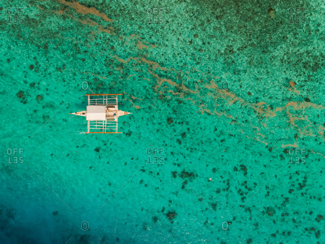 Aerial view of traditional filipino fishing boat by Sumilon island, Philippines.