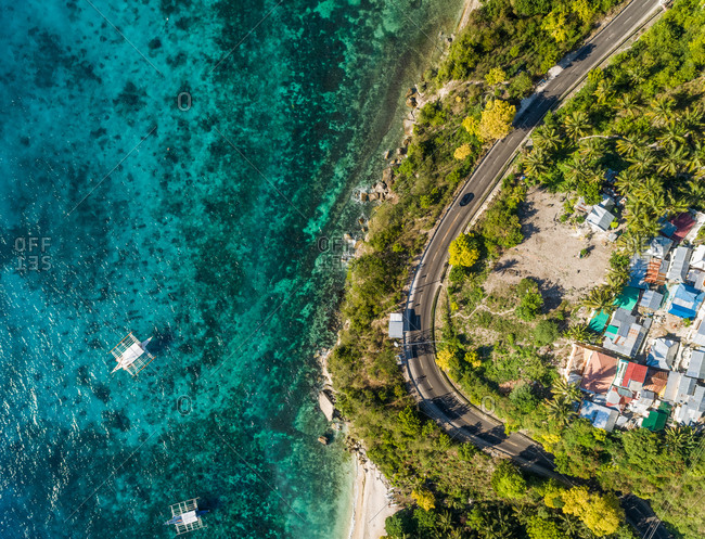 Aerial view of winding coastal road and boats in Oslob, Philippines.