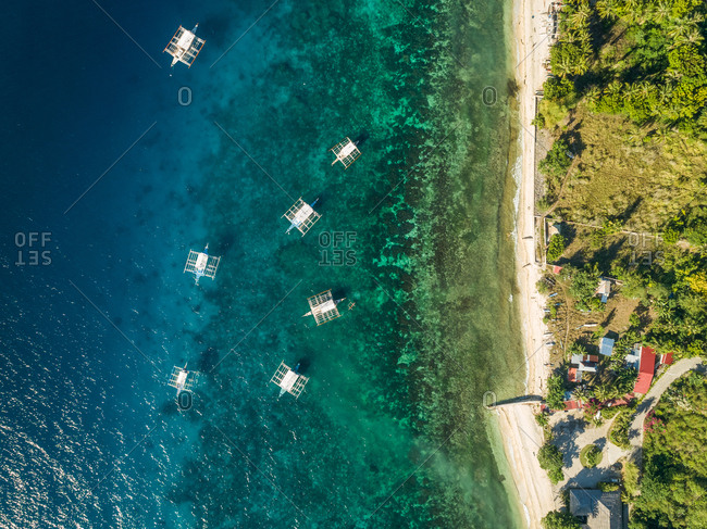 Aerial view of filipino boats and coastal road in Oslob, Philippines.