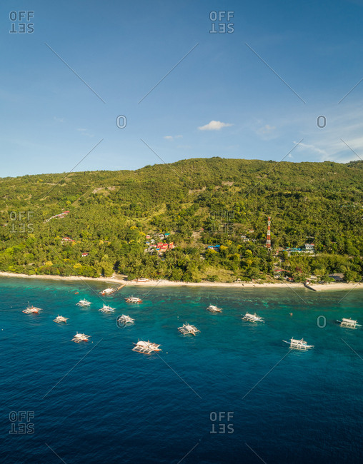 Aerial view of filipino boats, coastline and forest near Oslob, Philippines.