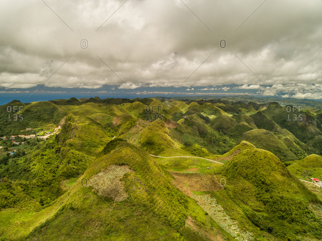 Aerial view of Chocolate hills and cloudy sky in Badian, Philippines.