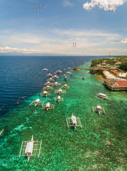 Aerial view of resort, coral reef and filipino boats, Moalboal, Philippines.