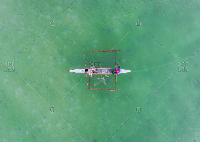 Aerial view of couple fishing and traditional filipino boat, Dauis, Philippines.