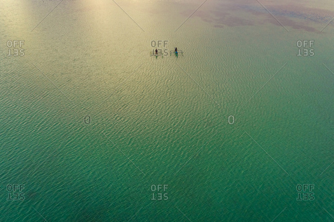 Aerial view of two men in traditional  outrigger boats, Dauis, Philippines.