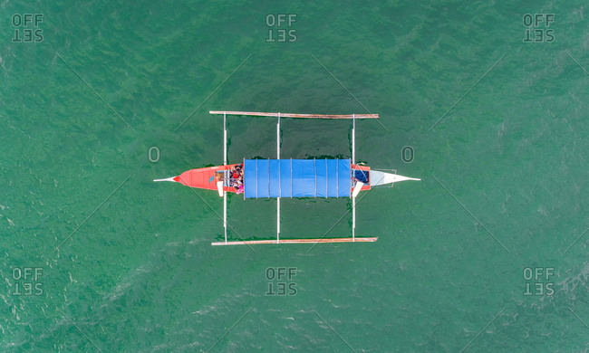 Aerial view of single boat in turquoise waters near Talisay, Philippines.
