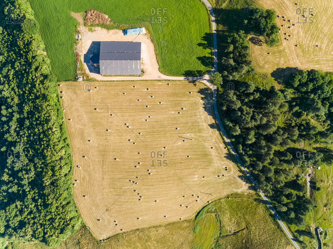 Aerial view of barn and straw bales in field in Correze, France.